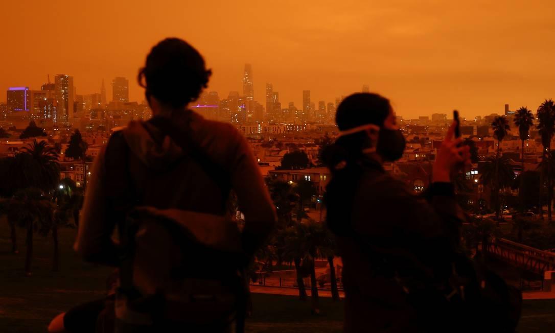 Os visitantes são vistos no Dolores Park sob um céu laranja escurecido pela fumaça dos incêndios florestais que já duram há semanas nos EUA Foto: Stephen Lam / REUTERS