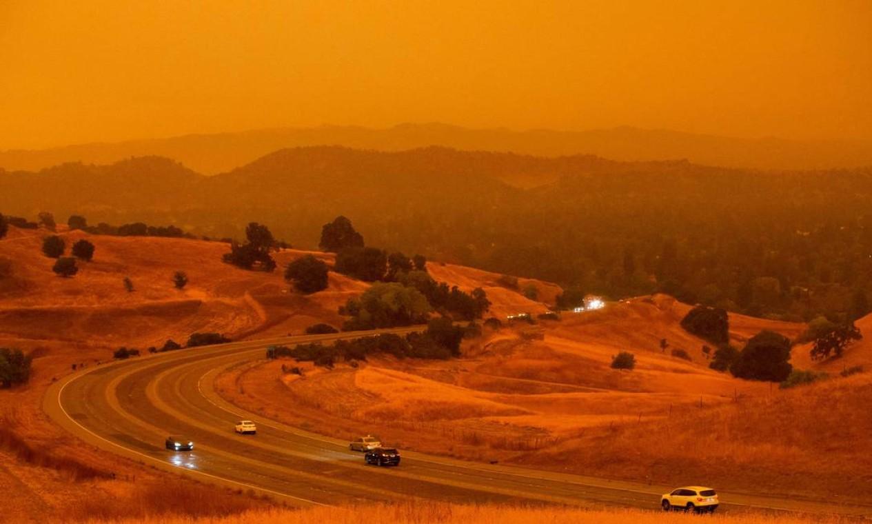 Carros passam ao longo da Ygnacio Valley Road sob céu laranja cheio de fumaça de incêndio florestal em Concord, Califórnia Foto: Brittany Hosea-Small / AFP