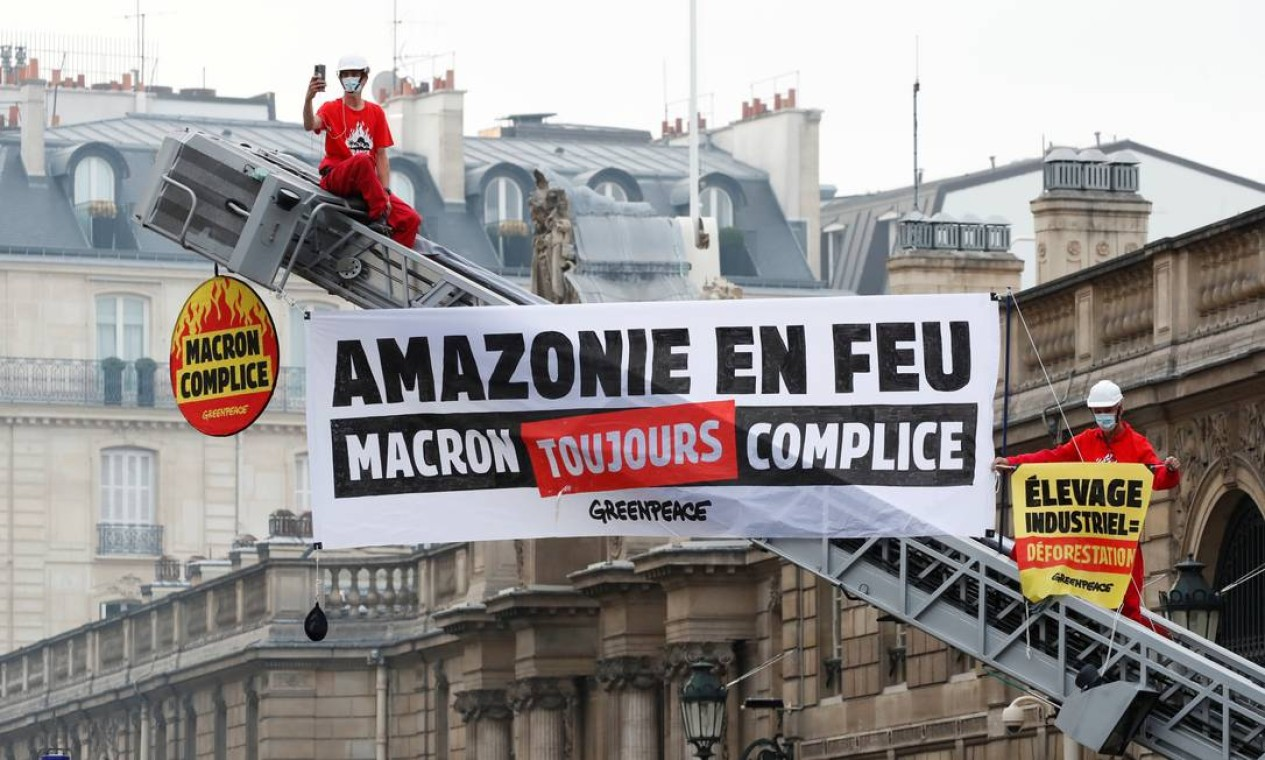 """Ativistas do Greenpeace subiram na escada retrátil de um caminhão de bombeiros durante uma ação em frente ao Palácio do Eliseu para protestar contra os danos contínuos à floresta amazônica, em Paris, França. O cartaz diz """"Floresta Amazônica em chamas. Macron sempre cúmplice"""" Foto: CHRISTIAN HARTMANN / REUTERS"""