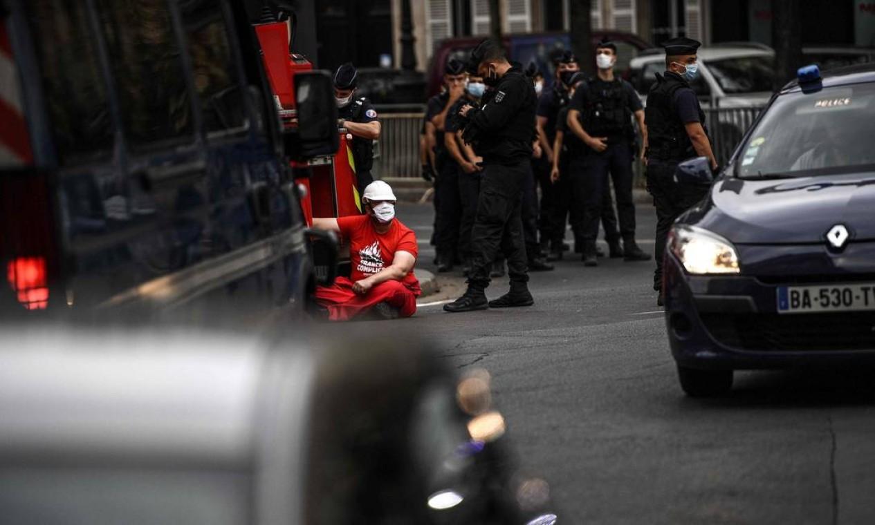 Polícia francesa se reúne enquanto um ativista do Greenpeace se acorrenta a um caminhão de bombeiros em frente ao Palácio do Eliseu, em Paris Foto: CHRISTOPHE ARCHAMBAULT / AFP