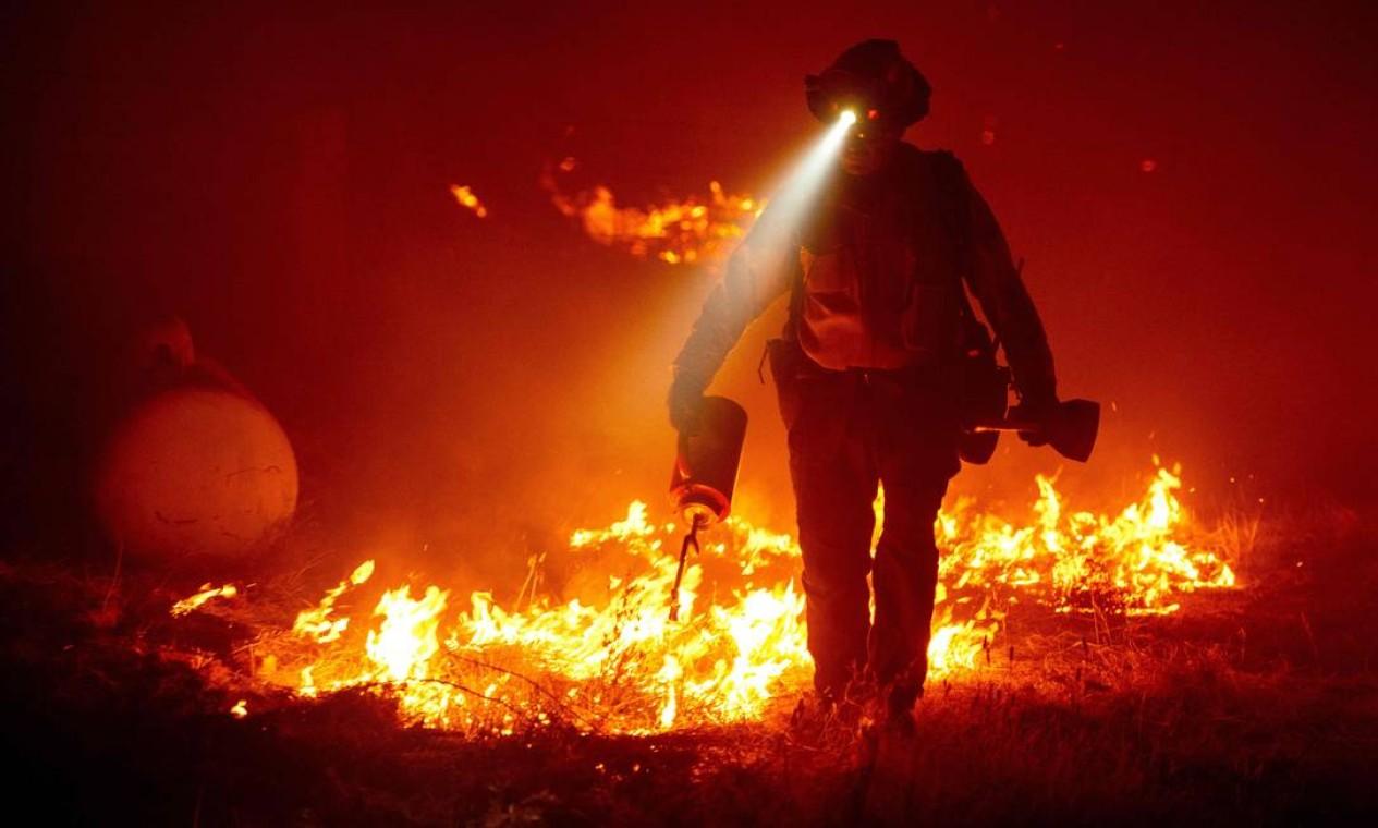 Bombeiro tenta apagar incêndio que atinge área próxima ao condado de Butte, na Califórnia Foto: JOSH EDELSON / AFP