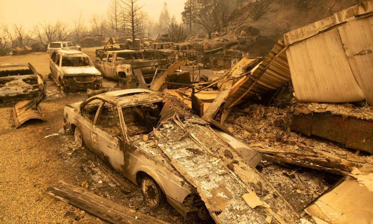 Veículos queimados ardem em uma residência durante o incêndio em Creek, em uma área não incorporada de Fresno County, Califórnia Foto: JOSH EDELSON / AFP