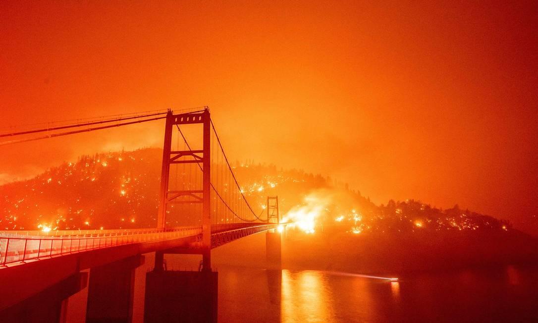 Bidwell Bar Bridge é cercada por fogo no Lago Oroville durante o incêndio do Bear em Oroville, Califórnia Foto: JOSH EDELSON / AFP