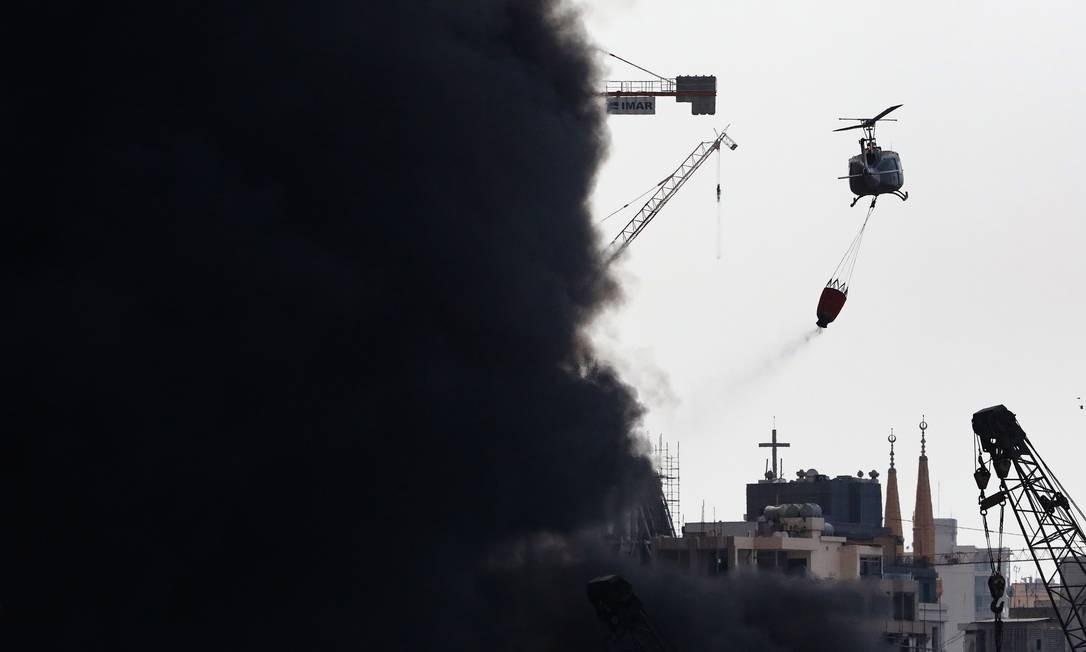 Um helicóptero do exército libanês despeja água sobre um grande incêndio no porto marítimo da capital libanesa Foto: ANWAR AMRO / AFP