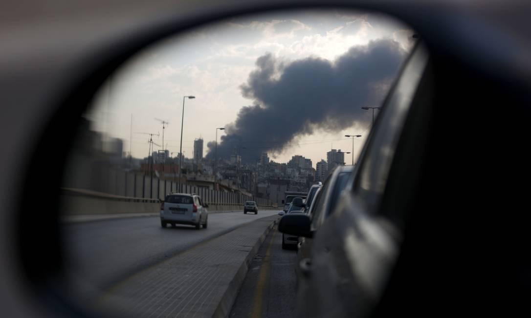 A fumaça provocada pelo incêndio no porto da capital libanesa é vista no retrovisor de um carro enquanto ele dirige por uma estrada próxima Foto: PATRICK BAZ / AFP