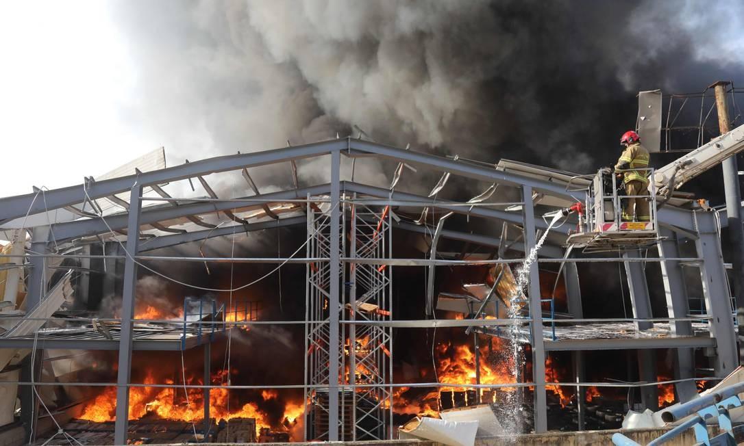 Bombeiro tenta apagar um incêndio no porto de Beirute, onde armazéns e silos de concreto que armazenam grãos foram destruídos pela explosão de 4 de agosto Foto: ANWAR AMRO / AFP