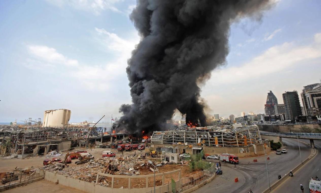 As chamas irromperam na zona franca do porto, erguendo uma enorme coluna de fumaça sobre a cidade Foto: ANWAR AMRO / AFP