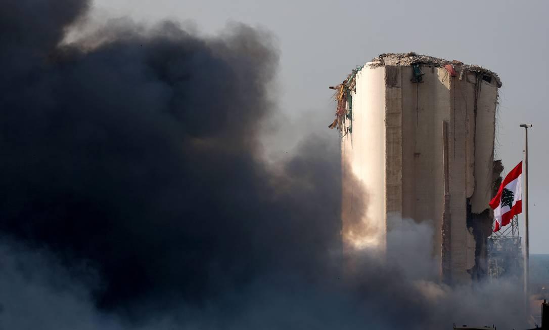 A bandeira libanesa está hasteada ao lado do silo do porto de Beirute, danificado na explosão de 4 de agosto, enquanto a fumaça sobe de um grande incêndio nesta quinta Foto: PATRICK BAZ / AFP