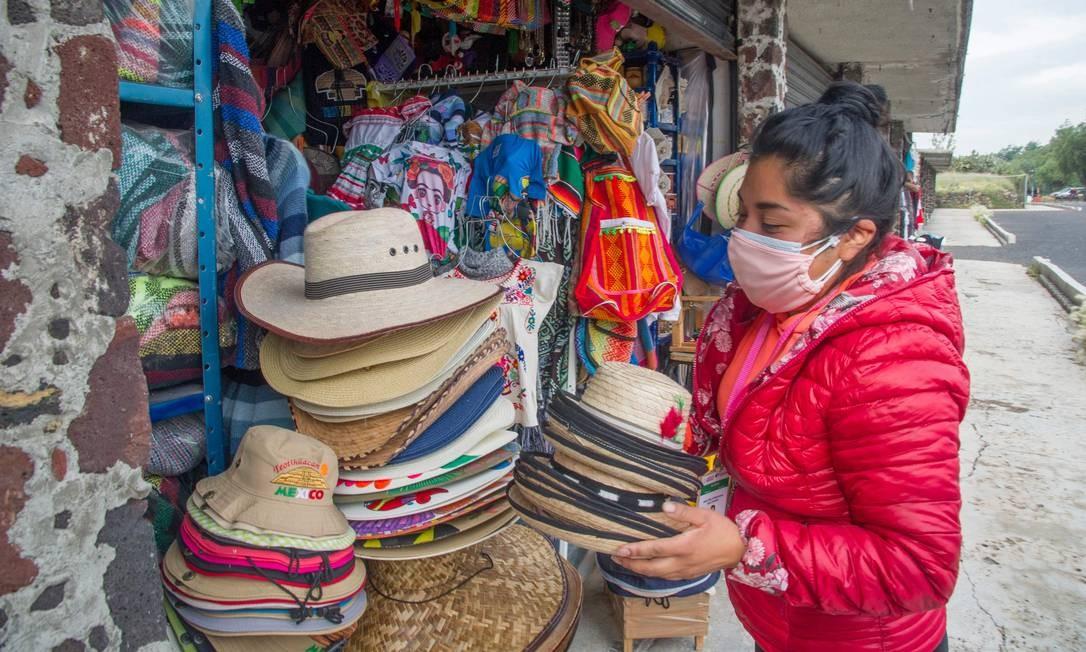 Um vendedor de artesanato coloca chapéus em exposição no sítio arqueológico de Teotihuacán Foto: CLAUDIO CRUZ / AFP