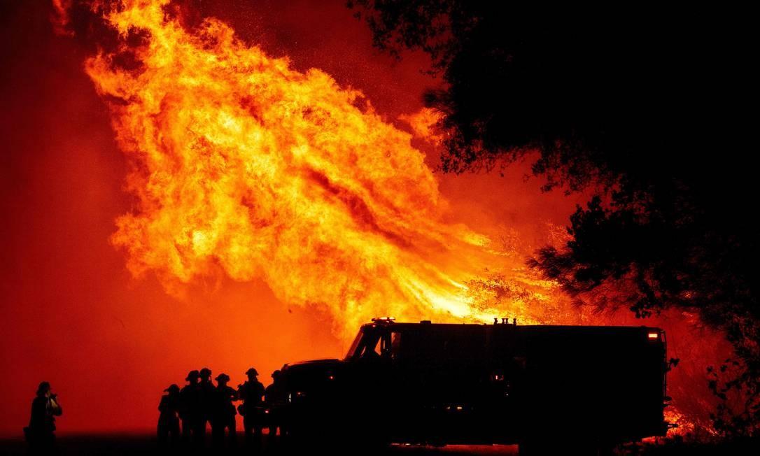 Bombeiros assistem a chamas gigantescas do Bear Fire, um dos maiores incêndios registrados na Califórnia Foto: JOSH EDELSON / AFP