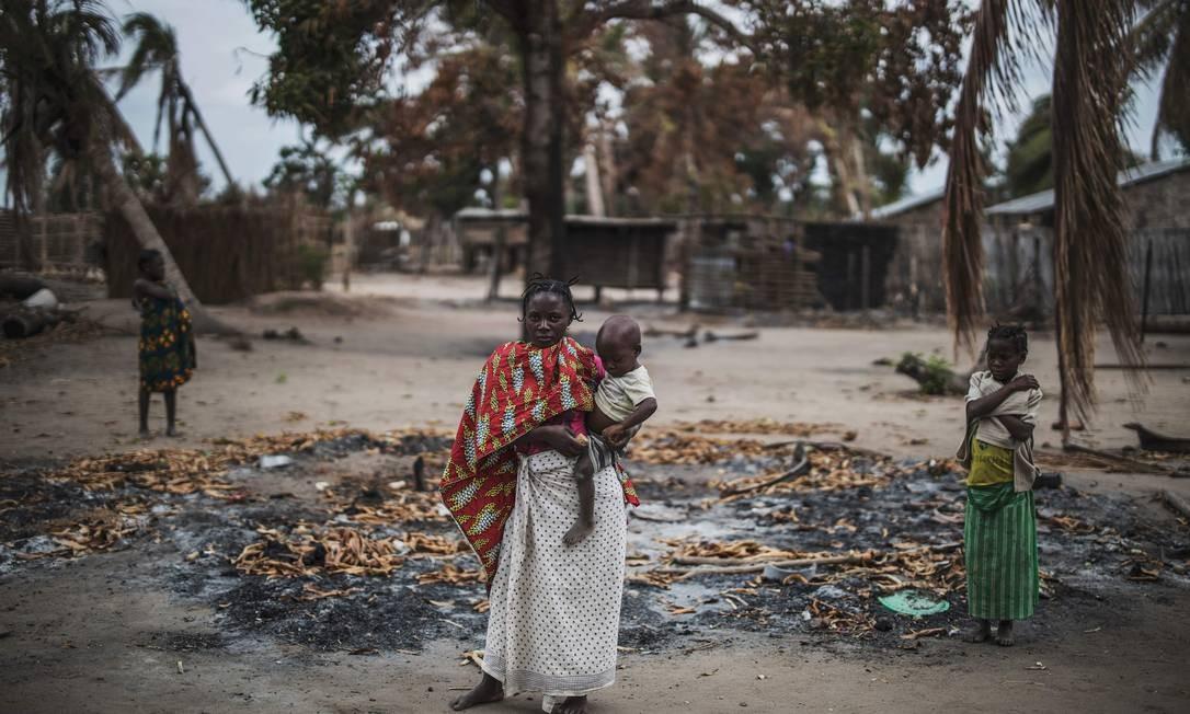 Mulher segura criança depois de ataque contra a aldeia onde ela morava, no Norte de Moçambique Foto: MARCO LONGARI / AFP