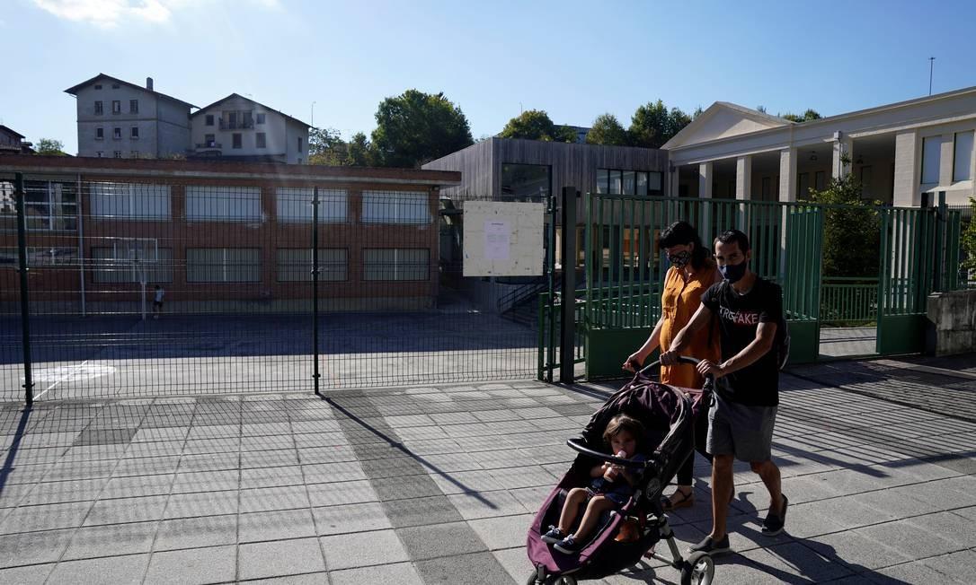 Casal caminha com criança em carrinho em frente a uma escola fechada no País Basco, na Espanha, na última quinta-feira (10); instituições foram fechadas na região depois que diversos professores testaram positivo para a Covid-19 Foto: VINCENT WEST / REUTERS