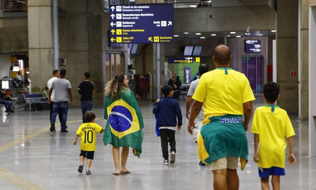 Com roupas verde e amarelas, passageiros caminham pelo Aeroporto Internacional do Galeão, no Rio de Janeiro Foto: Uanderson Fernandes / Agência O Globo / 8-7-2018