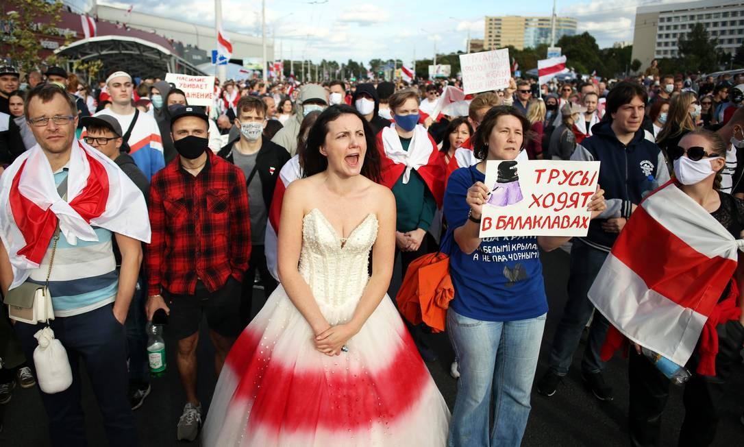 """Manifestantes exibem um cartaz com os dizeres """"Covardes usam balaclavas"""" em protesto contra o uso da força policial na Bielorrússia contra manifestantes pacíficos Foto: - / AFP"""