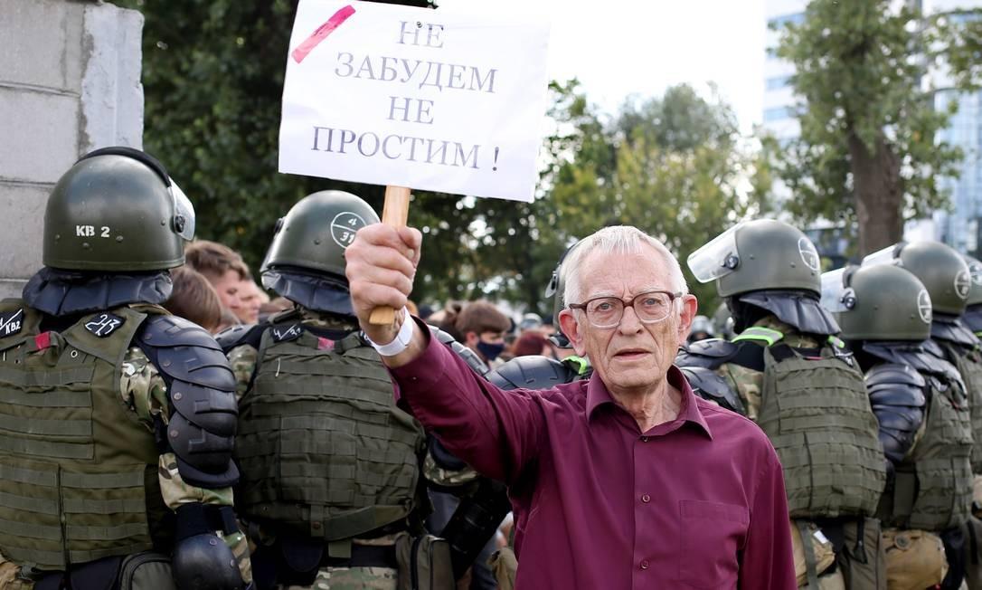 """Um homem segura um cartaz com os dizeres """"Não esqueceremos, não perdoaremos!"""" Foto: - / AFP"""