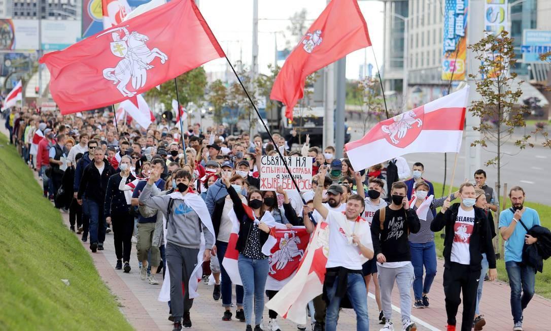 Apoiadores da oposição desfilam pelas ruas de Minsk para exigir renúncia do presidente, acusado de fraudar as eleições presidenciais de 9 de agosto Foto: VADIM ZAMIROVSKI / AFP