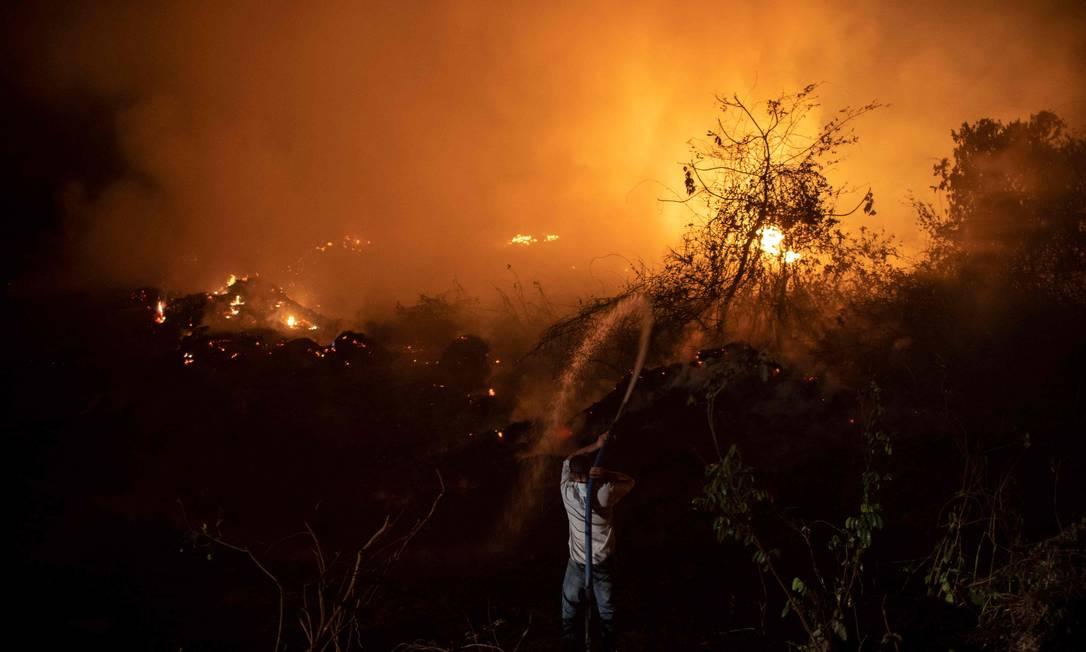 Um voluntário joga água para controlar um incêndio usando um caminhão-pipa para proteger uma ponte de madeira – uma das 119 existentes na Estrada do Parque da Transpantaneira – no Pantanal Foto: MAURO PIMENTEL / AFP - 13/09/2020