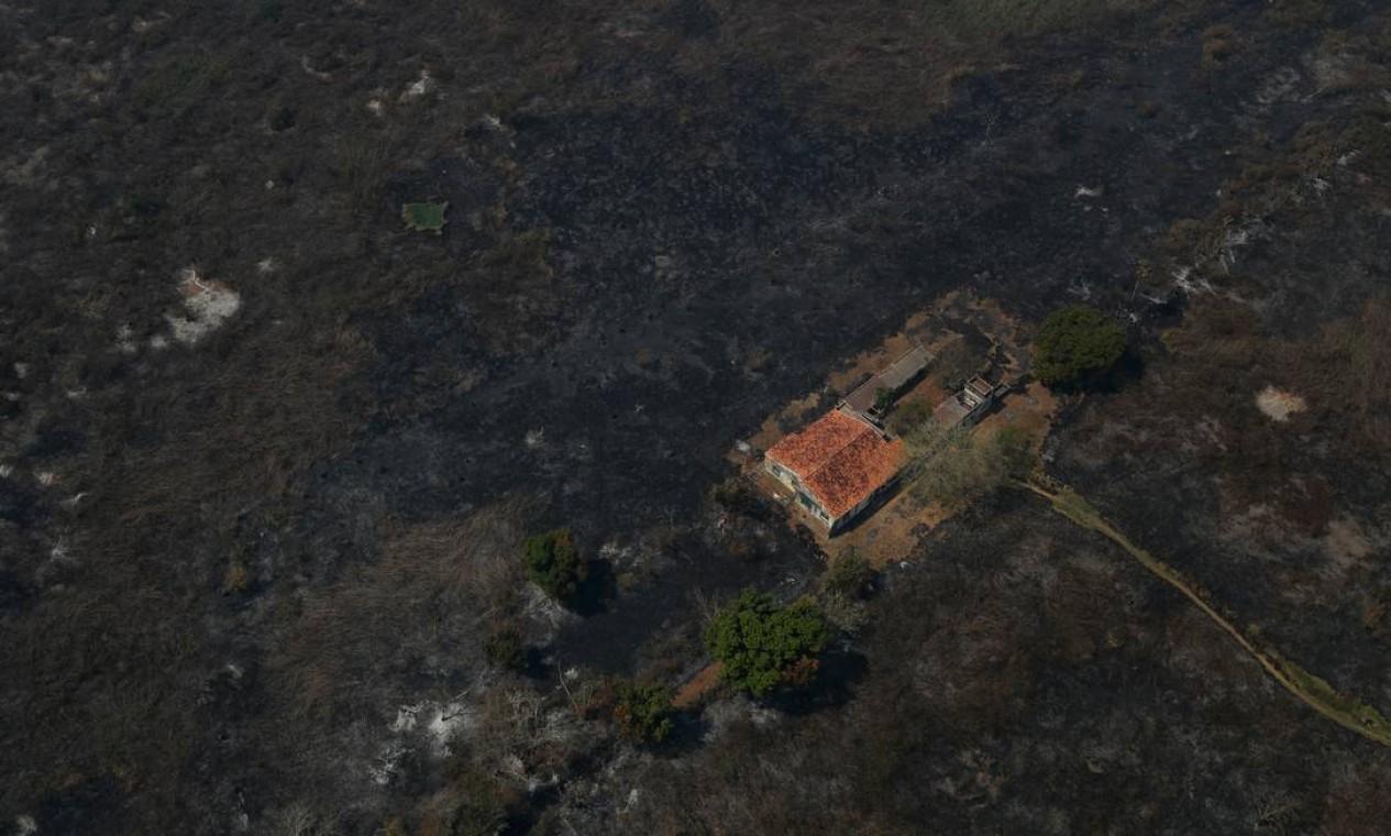 Vista aérea de uma casa cercada por vegetação queimada no Pantanal, em Pocone, no Mato Grosso. Dados do Centro Nacional de Prevenção e Combate aos Incêndios Florestais (Prevfogo) apontam que uma área equivalente a 2,2 milhões de hectares foi consumida pelas queimadas, o equivalente a 15% do bioma Foto: AMANDA PEROBELLI / REUTERS - 28/08/2020