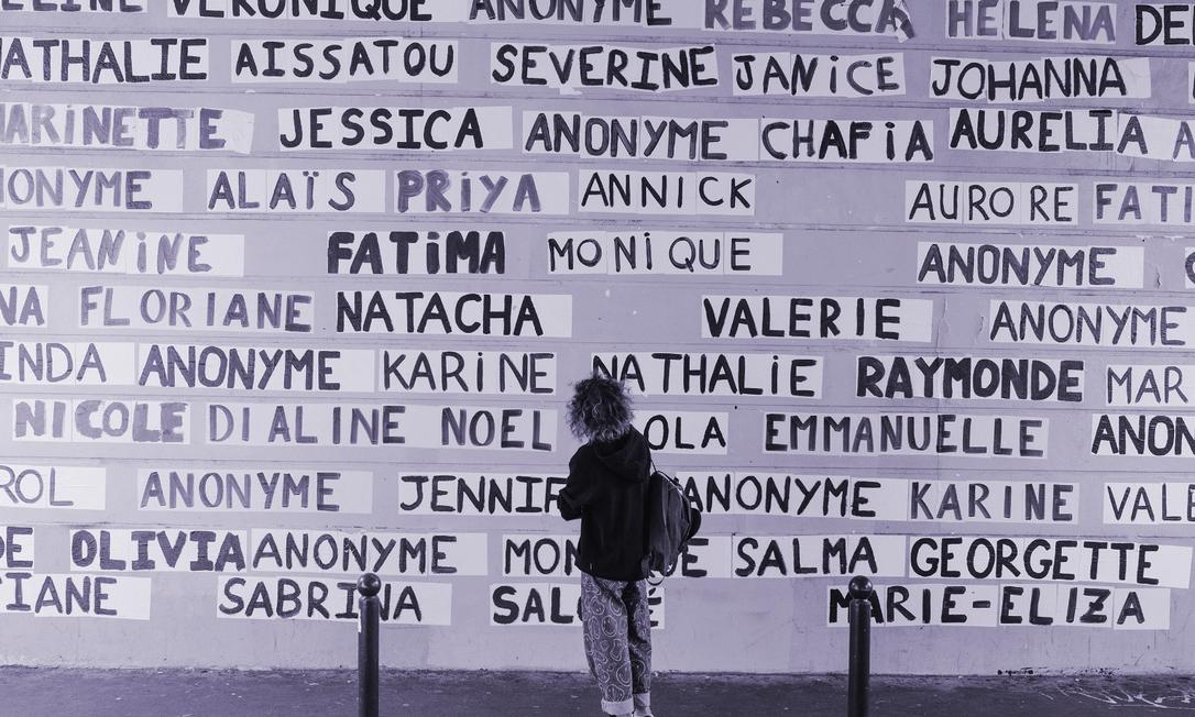"""Uma mulher olha um muro coberto com os nomes de vítimas de feminicídio em Paris. A campanha de um grupo que se intitula """"As coladoras"""" usa cartazes para denunciar a violência contra as mulheres e tem se tornado uma ferramenta efetiva de conscientização Foto: DMITRY KOSTYUKOV/NYT"""