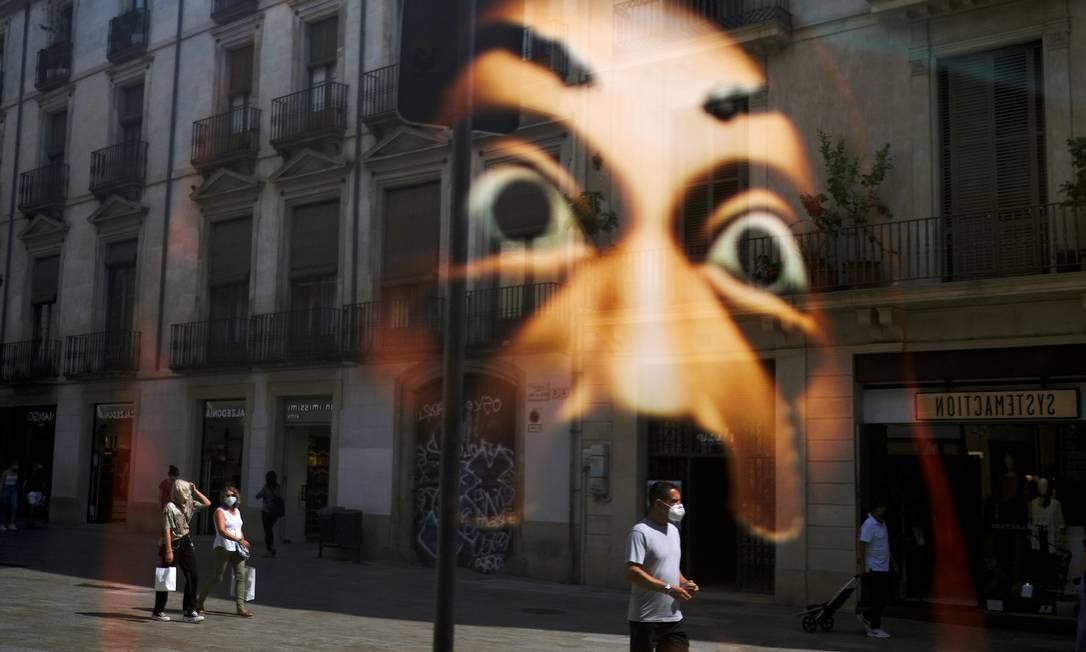 Pessoas usando máscaras são refletidas na vitrine de uma loja enquanto caminham por uma rua do Barri Gòtic (Bairro Gótico), depois que autoridades regionais da Catalunha anunciaram restrições para conter a propagação do coronavírus, em Barcelona, Espanha Foto: NACHO DOCE / REUTERS