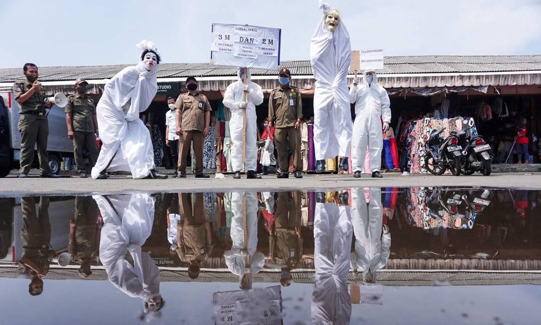 Funcionários do governo local vestem fantasias de Pocong, uma das famosas figuras fantasmas da Indonésia, para fazer campanha pelos perigos do coronavírus, em um mercado tradicional na província de Tangerang Banten Foto: ARYA MANGGALA / AFP