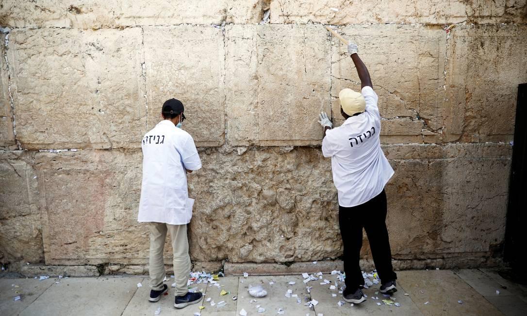 Trabalhador desinfeta o Muro das Lamentações, o local de oração mais sagrado do judaísmo, antes do Ano Novo judaico, em meio à crise docoronavírus, em Jerusalém Foto: RONEN ZVULUN / REUTERS