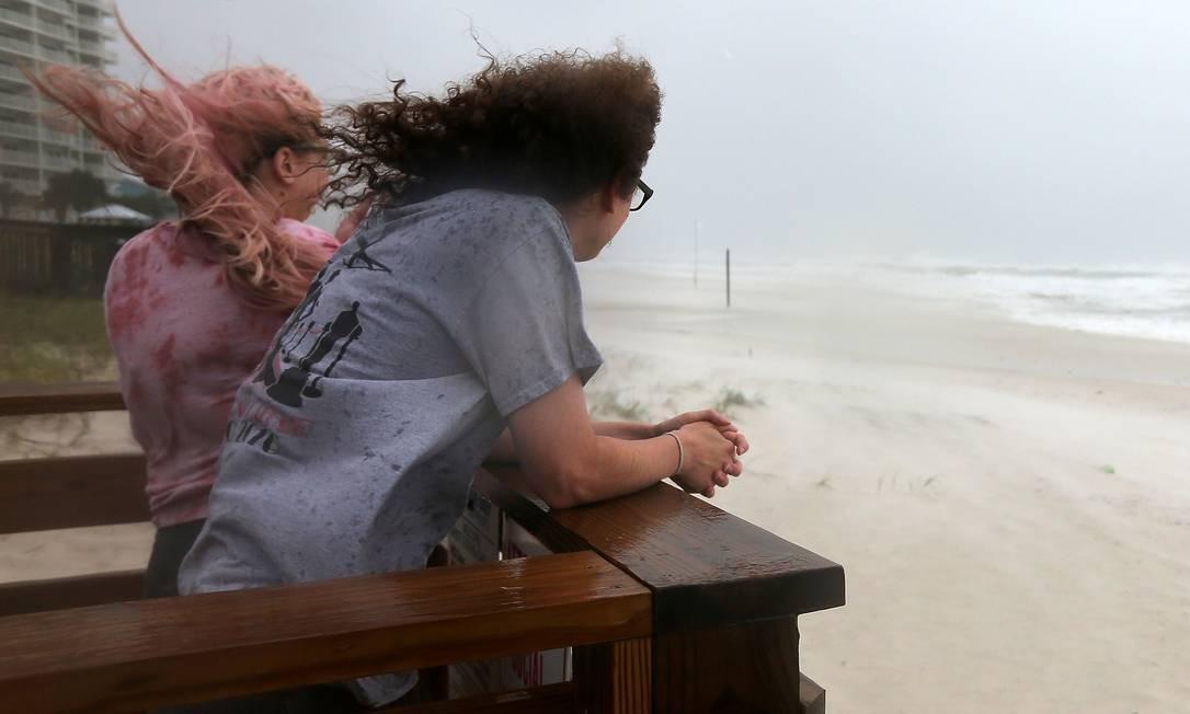 Duas mulheres observam as ondas chegarem à costa com a aproximação do furacão Sally em Orange Beach, Alabama, nos EUA Foto: JONATHAN BACHMAN / REUTERS