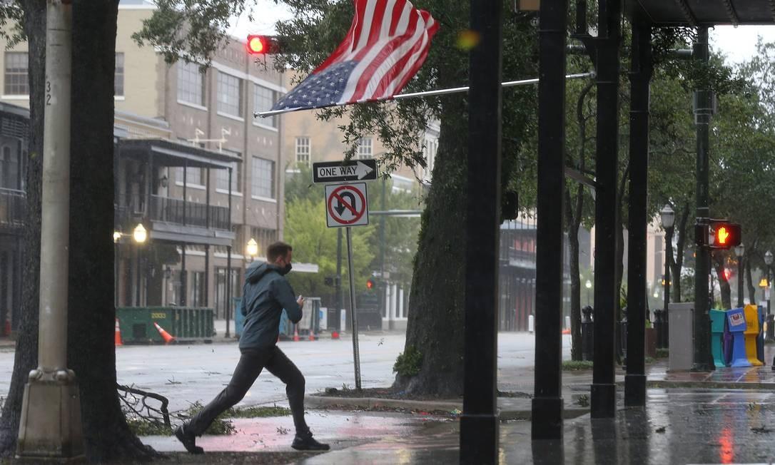 Um homem passa por uma bandeira americana durante o furacão Sally na cidade de Mobile, no Alabama Foto: JONATHAN BACHMAN / REUTERS