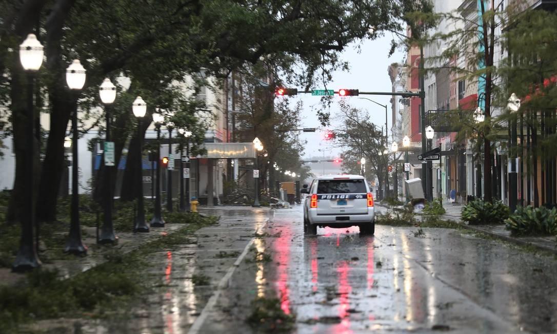 Viatura policial passa por uma rua repleta de galhos quando ventos e chuva causados pelo furacão Sally atingem a cidade de Mobile, Alabama Foto: JOE RAEDLE / AFP