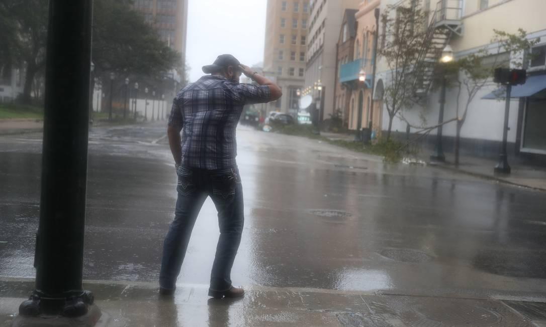 Homem tenta resistir aos ventos e à chuva do furacão Sally na cidade de Mobile, no Alabama Foto: JOE RAEDLE / AFP