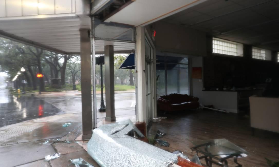 Uma janela quebrada é vista após a passagem do furacão Sally Foto: JOE RAEDLE / AFP