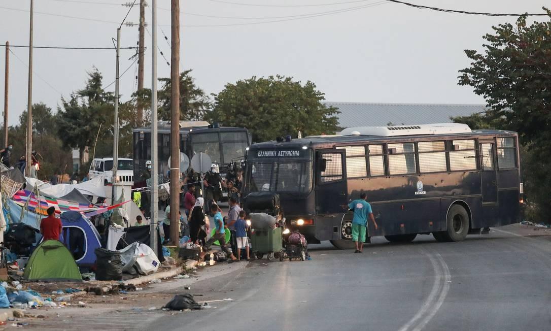 Policiais gregos usam ônibus para recolher refugiados que serão levados para um novo campo na ilha de Lesbos Foto: ELIAS MARCOU / REUTERS