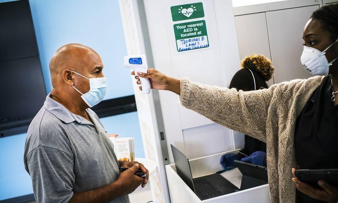 Passageiro tem sua temperatura medida num centro de testagem no Newark Liberty International Airport, em Nova Jersey Foto: Eduardo Muñoz Alvarez / AFP
