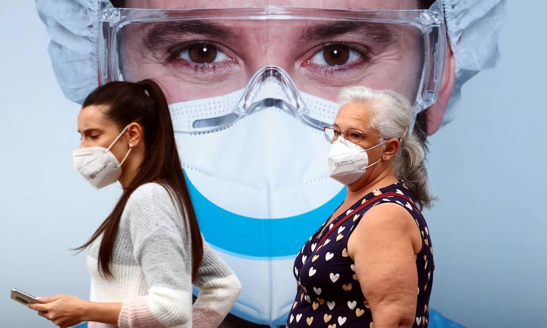 Duas mulheres caminham em Madri utilizando máscara Foto: Sergio Perez / Reuters