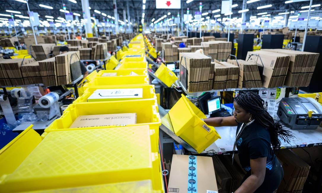 """Nos depósitos da Amazon, """"os livros estão guardados ao lado de torradeiras, brinquedos ou skates"""", escreve Jordi Carrión no livro """"Contra a Amazon"""". Na foto, funcionários preparam encomendas em um depósito da empresa americana em Nova York Foto: JOHANNES EISELE / AFP"""