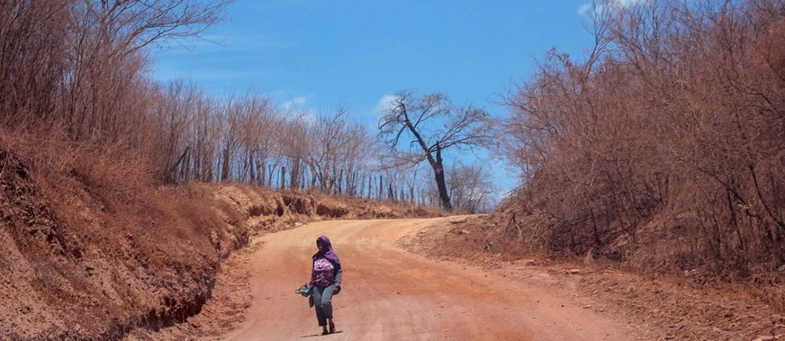 Mulher caminha em direção a Guaribas por estrada de terra. Foto: Manoel Ventura / Agência O Globo