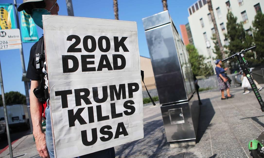"""""""200 mil mortos. Trump mata os EUA"""", diz a placa de um manifestante em Los Angeles, na California, durante um protesto em 21 de setembro contra a atuação de Trump na pandemia Foto: Mario Tama / AFP"""