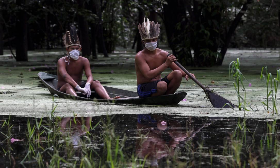 Satere-mawe indigenous men Indígenas satere-mawe navegam com máscaras pelo rio Ariau, na comunidade Sahu-Ape, a 80 quilômetros de Manaus (AM), em foto de maio Foto: RICARDO OLIVEIRA / AFP
