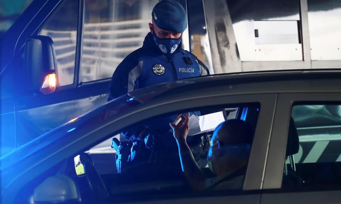 Policial checa documentação de uma pessoa em uma das áreas de Madri onde o movimento foi restringido por causa do aumento de casos de Covid-19 Foto: Sergio Perez / Reuters