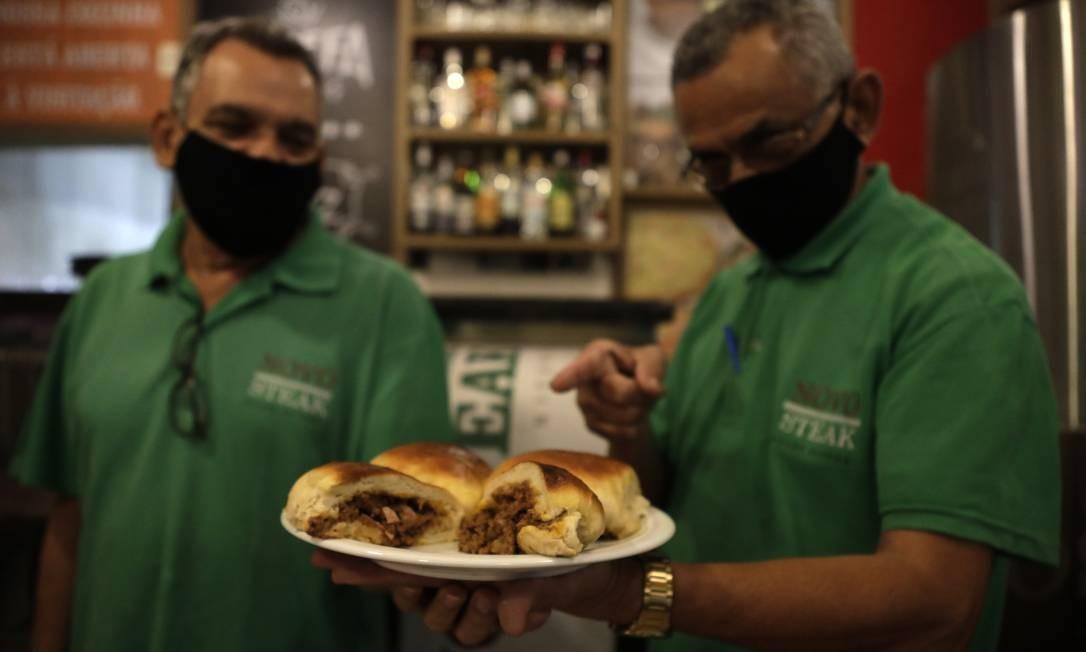 Francisco Costa (à esquerda) e José Santos, garçons do Novo Steak, com uma porção do salgado: recheio de queijo, presunto e carne moída. Foto: Agência O Globo / Luiza Moraes