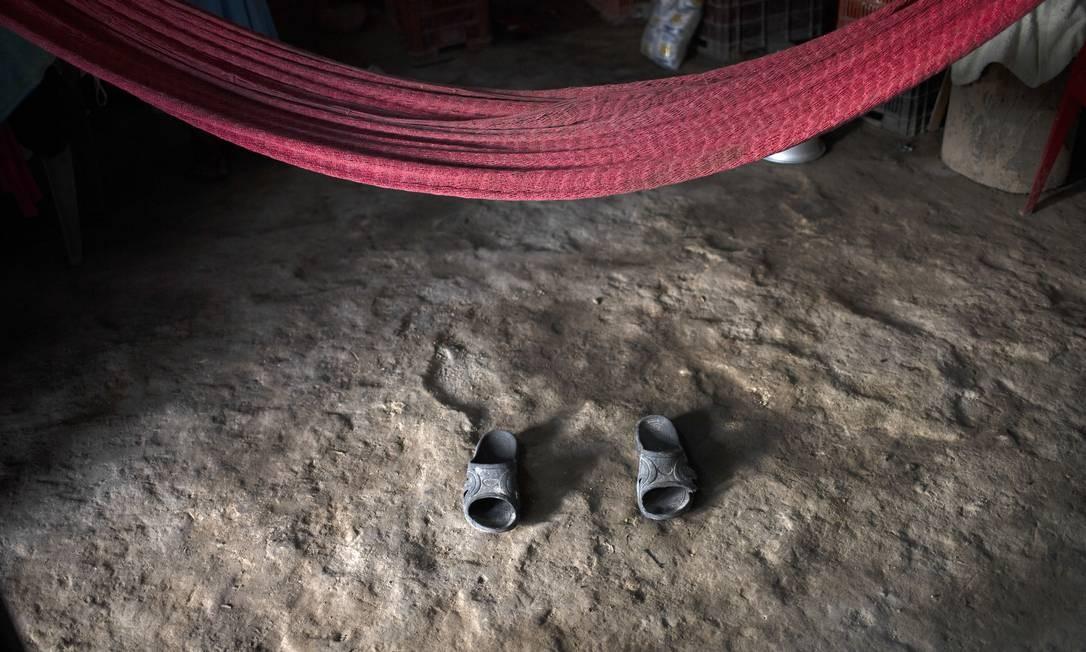 Um par de sandálias sob uma rede, que pertencia a Joaquin Barrera, vítima da Covid-19, é vista em sua casa, em Santiago Nonualco, El Salvador. Mortes pelo coronavírus atingiram a marca de um milhão no mundo. Cerca de um terço delas ocorreram na América Latina, onde países com recursos médicos sobrecarregados se preparam para uma nova onda de contágio Foto: YURI CORTEZ / AFP