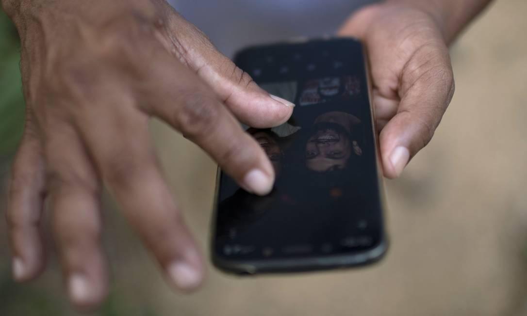 O taxista Márcio Silva, de 56 anos, mostra na tela de seu celular um retrato dele e de seu filho falecido, vítima da COVID-19, Hugo Dutra, 25 anos, no Quilombo Sacopã, no Rio de Janeiro Foto: MAURO PIMENTEL / AFP