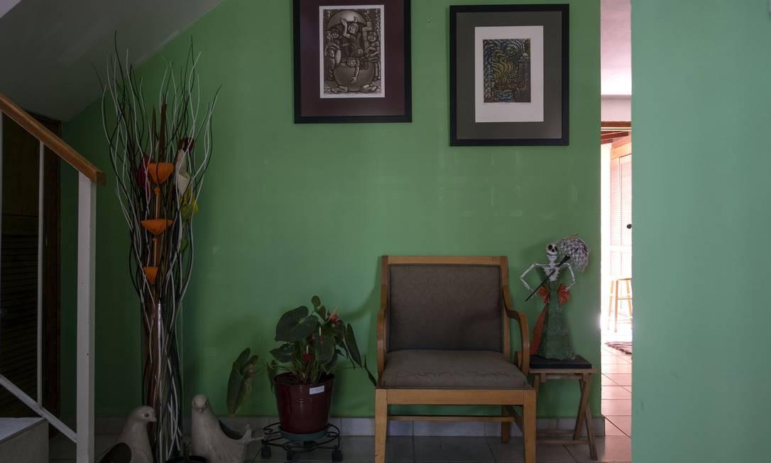 Uma cadeira, uma planta, pinturas e uma figura de Catrina, todas pertencentes a Hebert Axel Gonzalez, um diretor de teatro que morreu de COVID-19 em abril, agora decoram a entrada da casa de seu sócio, Carlos Corro, em Tijuana, Estado da Baixa Califórnia, México Foto: GUILLERMO ARIAS / AFP