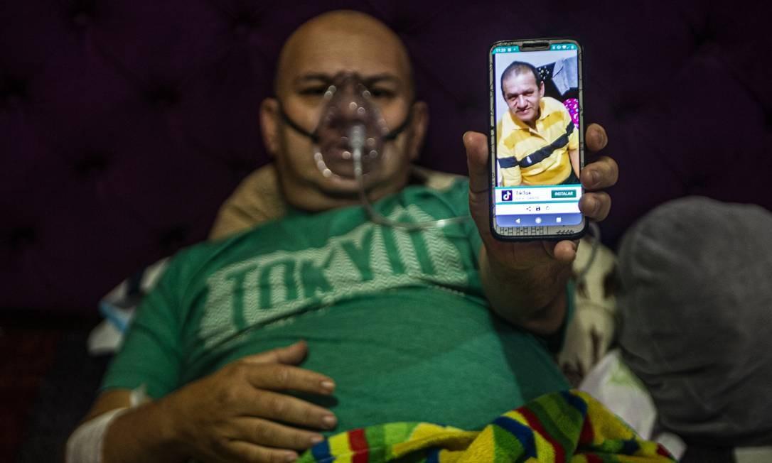 O venezuelano Wilmer Hernandez, 44, mostra uma foto de seu pai, Wilmer Arcadio Hernandez, 63, enquanto ele permanece conectado a um tanque de oxigênio em sua casa, em Villa Maria del Triunfo, ao sul de Lima Foto: ERNESTO BENAVIDES / AFP