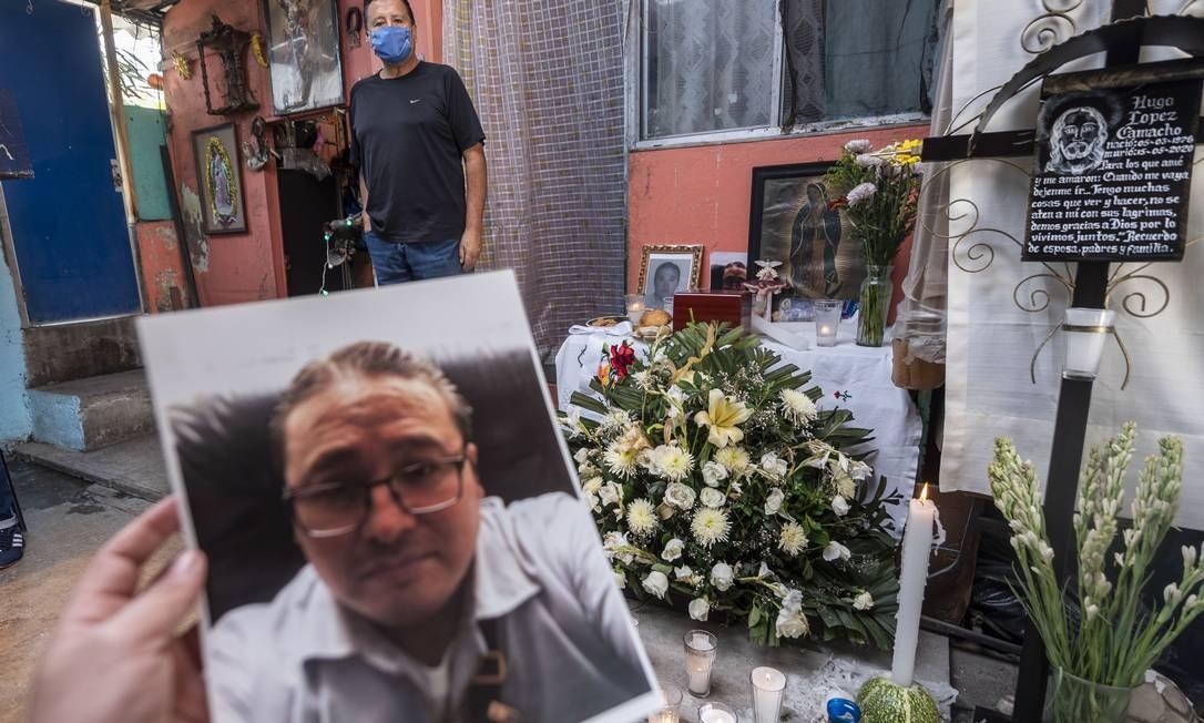 Um parente mostra uma foto do mexicano Hugo Lopez Camacho, que morreu pela COVID-19, durante uma missa após sua morte, na Cidade do México Foto: PEDRO PARDO / AFP