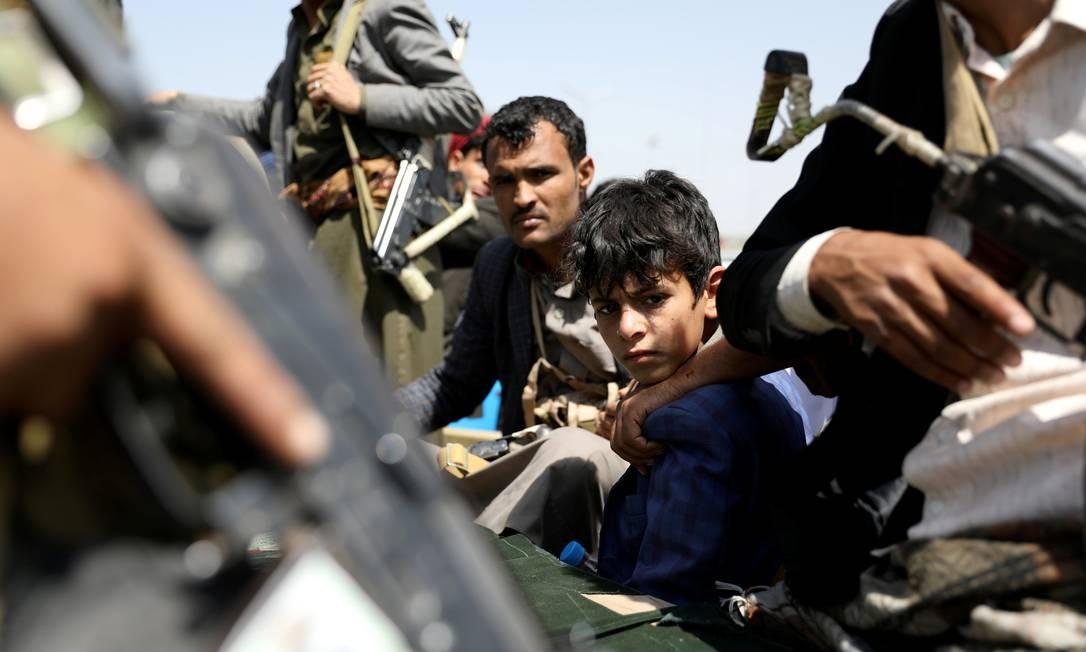 Rebeldes houthis, entre eles um menino, patrulham o funeral de seus combatentes mortos em Sanaa, no Iêmen Foto: KHALED ABDULLAH / REUTERS/22-09-2020