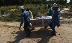 Parentes e coveiros levam o corpo de uma vítima da Covid-19 em Nova Délhi, na Índia Foto: SAJJAD HUSSAIN / AFP