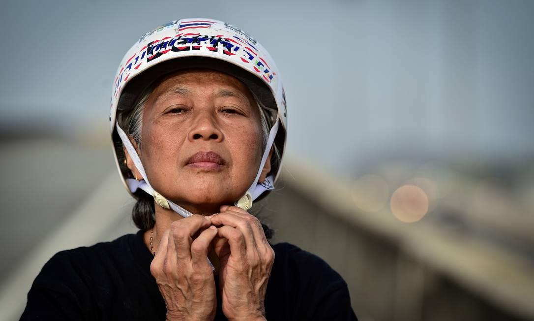 Nongluck Chairuettichai, também conhecida como Jeab, coloca um capacete antes de uma sess?o de treinos na capital Bangkok Foto: LILLIAN SUWANRUMPHA / AFP