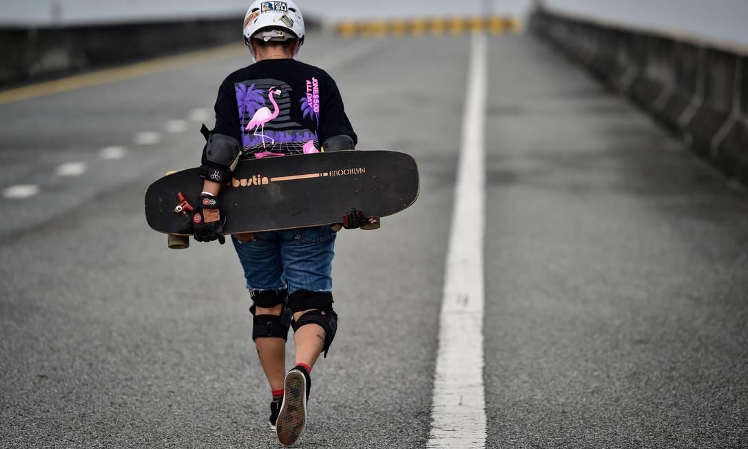 Para ela, o longboard é um exercício completo. Se balan?? e se divertir nas descidas e caminhar nas subidas garantem a boa forma e a saúde mental Foto: LILLIAN SUWANRUMPHA / AFP