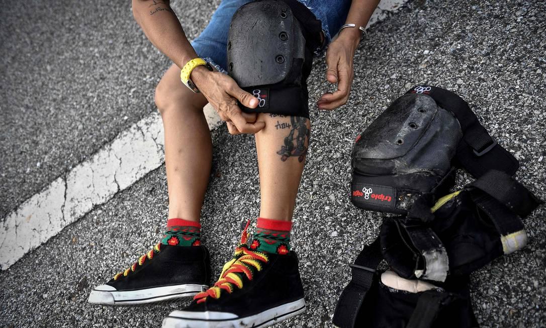 Jeab veste joelheiras para andar de longboard, esporte que conheceu há 10 anos, visitando um skate park com o filho Soteera Foto: LILLIAN SUWANRUMPHA / AFP